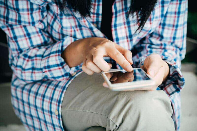 Una persona usa un smartphone mientras consume un vídeo en una plataforma online